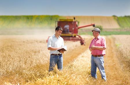 campesino: Campesino y hombre de negocios haciendo de acuerdo en campo de trigo