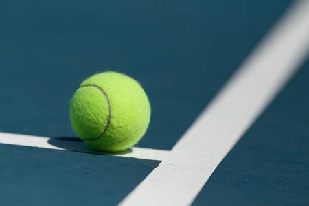 Tennis ball on blue hard court inside of line photo