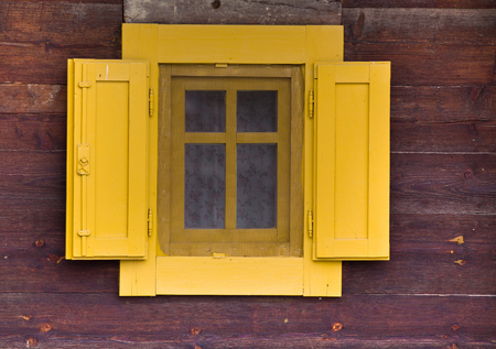 colord: Window with yellow shutters on the facade of an old wooden cottage
