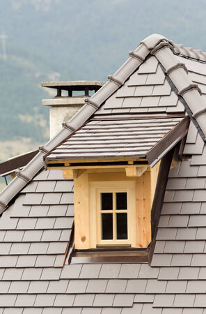 Wooden dormer on tiled roof on mountain house photo