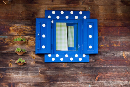 colord: Blue window with white spots on wooden wall of traditional village house Stock Photo