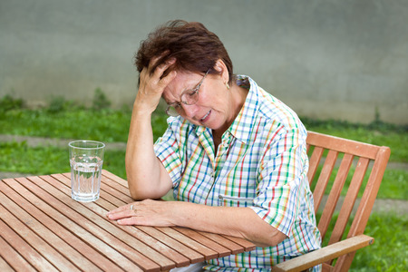 Senior woman suffers from headache, sitting at table with glass of water in front of her