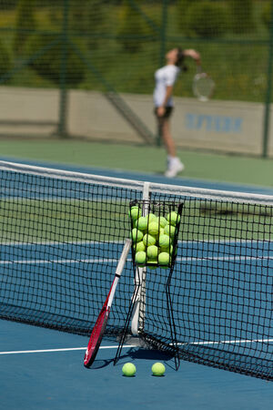 Tennis racket and balls in basket on blue hard court with tennis player in background photo