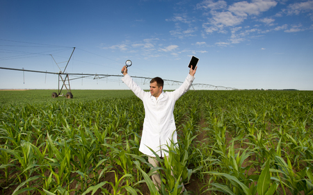 Satisfied agronomist standing with tablet and magnifier in raised hands in corn field photo
