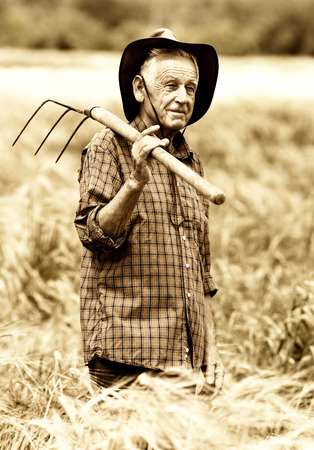 hayfork: Old photo of happy senior peasant after hard work in the field