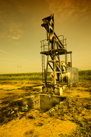 dug well: Oil pump jack in plains in sepia colors