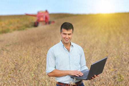 Young landowner with laptop supervising soybean harvesting work  Stok Fotoğraf