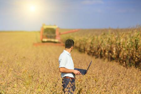 Giovane proprietario terriero con il computer portatile supervisione soia lavoro di raccolta