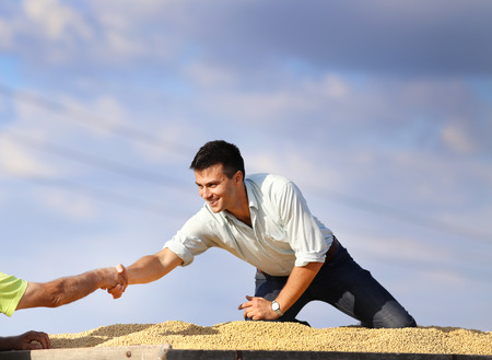 soybean: Young satisfied businessman sitting on soybeans heap and helping worker to climb on trailer Stock Photo
