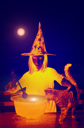 Young witch with cat boiling magic potion photo