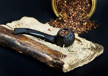 hedonism: Smoking pipe with smoking tobacco on very old book
