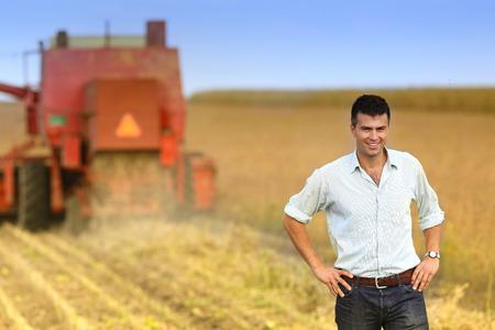 agricultura: Satisfecho empresario joven de pie en el campo de soja durante la cosecha Foto de archivo