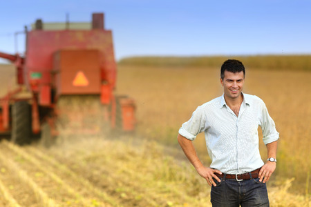 soybean: Young satisfied businessman standing on soybean field during harvesting