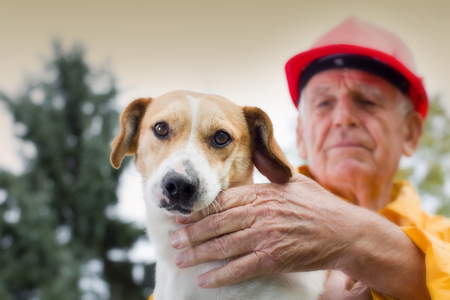 Old man rescuing dog from natural disaster
