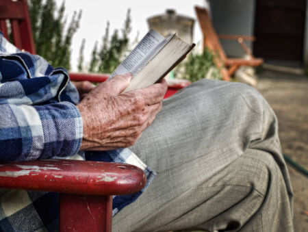 reading book: Close up of old mans hand holding a book for reading