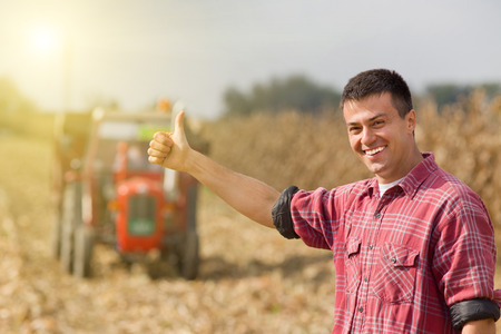 Young satisfied farmer showing thumbs up, tractor on field in background Banque d'images