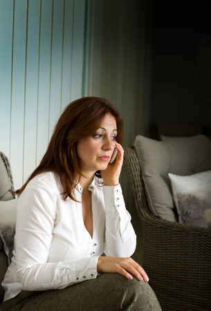 Worried middle aged woman talking on cell phone in living room