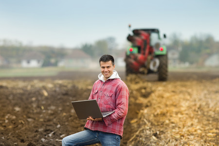 Young attractive peasant holding laptop in the field, tractor ploughing in the background