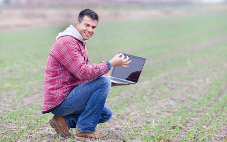 campesino: Campesino atractiva joven con pl�ntulas de monitoreo port�til en el campo