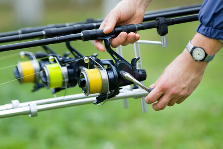 holding close: Close up of male hands holding fishing rod