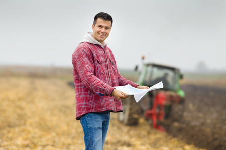 young farmer: Happy young farmer with forms for bank loan standing on field, tractor in background