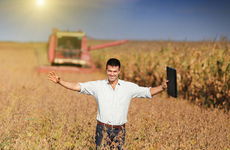 raised arms: Happy young landowner with raised arms and laptop standing on soybean field during harvest
