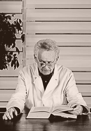 bata blanca: Foto vieja del hombre mayor en blanco libro de lectura abrigo en la oficina