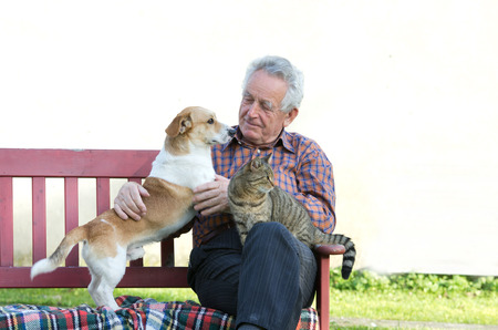 Älterer Mann, der mit Hund und Katze auf dem Schoß auf der Bank