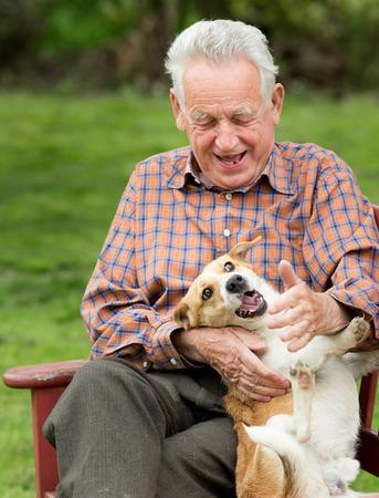 Alter Mann, der mit seinem Hund auf Bank im Garten