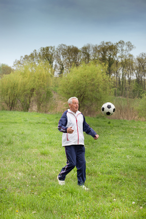 vejez feliz: Viejo hombre en setenta patear un bal�n de f�tbol en el parque
