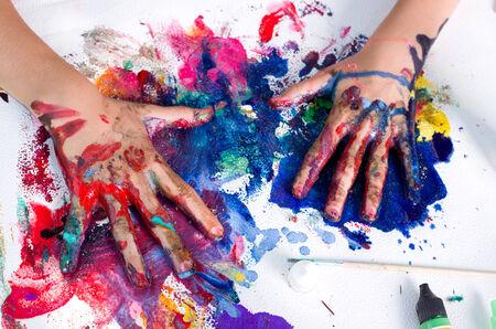 Geschilderde handen vlekken kleuren op rommelige papier Stockfoto