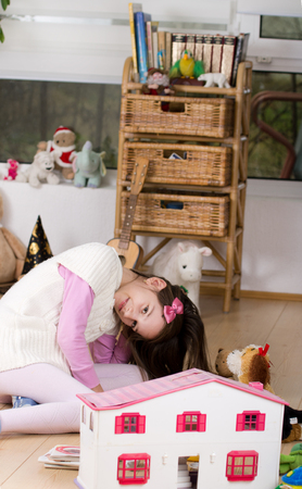 Young girl playing with stuffed animals and dolls house on the floor in her room photo