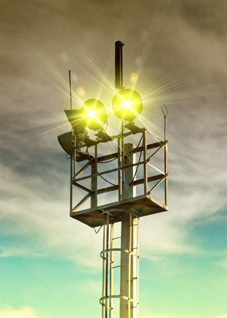 amp tower: Loudspeakers and reflector on metal column with sky in background