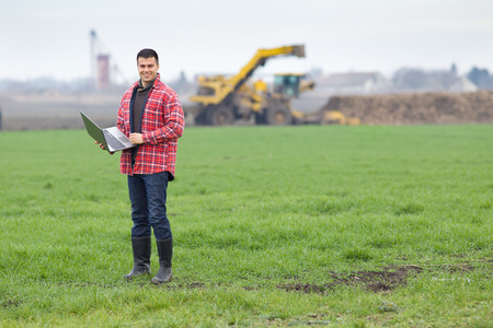 Attractive young peasant standing with laptop on farm