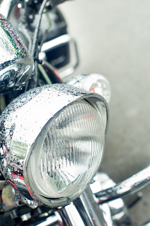 Close up of wet motorbike front light photo