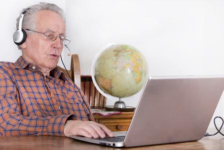 old home: Older man using laptop for internet communication