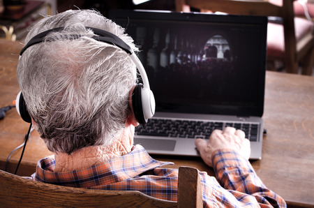 Old man with headset looking at laptop photo