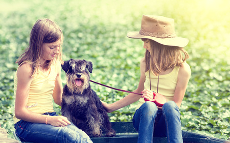 Two young girls sitting on boat with their dog, green background with sun rays photo