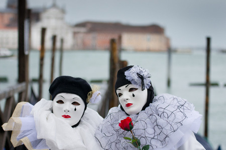 VENICE - MARCH 1: Two undefined persons wear Venetian costumes and attend the Carnival of Venice on St. Marks Square, 2014 in Venice, Italy photo