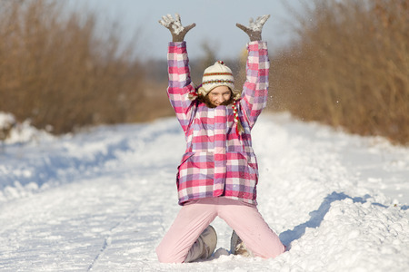 knees up: Happy young girl standing on knees and with hands up on snow