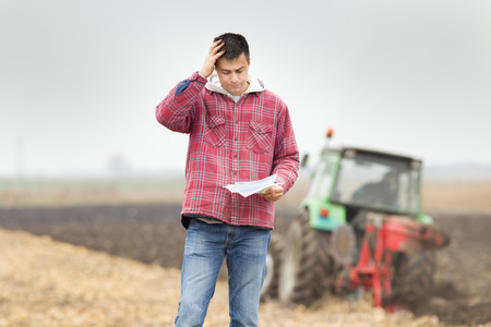 Worried young farmer standing on field and looking at papers from bank, tractor in background