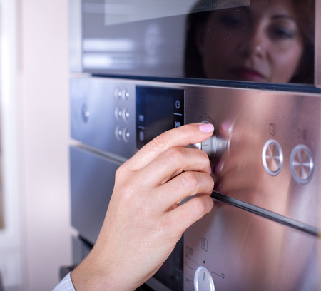 backing up: Close up of female hand turning on the oven in modern kitchen