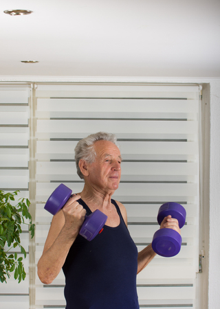 the seventies: Senior man in his seventies training and lifting weight Stock Photo