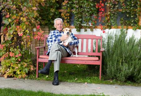 vejez feliz: Hombre mayor abrazando a su perro en su regazo en el banco