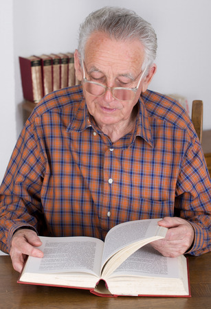 Old man with reading glasses reading book in his library photo