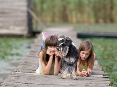 endear: Two girls lying on wooden dock with miniature schnauzer in front plan Stock Photo