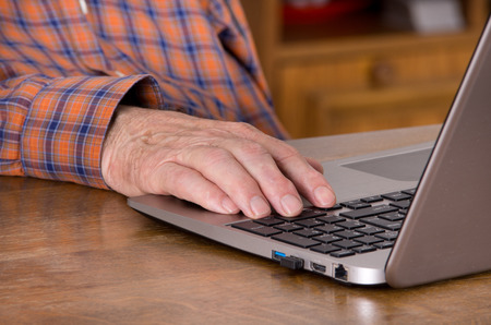 Close up of old male hand on keyboard of laptop photo