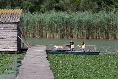 wooden dock: Two young girls with dogs sitting in boat next to wooden dock