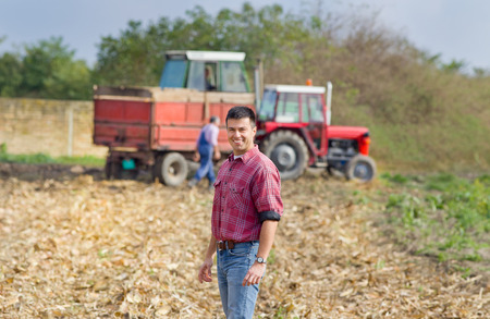 young farmer: Smiling young farmer standing on field with tractor and trailer in background Stock Photo