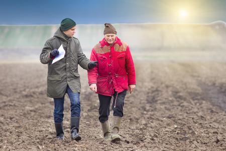farm worker: Two farmers walking on plowed field in winter time
